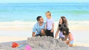 Joyful family building a sand castle