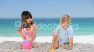 Cute children building a sand castle