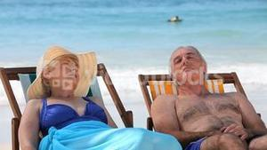 Elderly couple relaxing on beach chairs