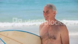 Elderly man looking at the horizon with a surfboard