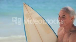Aged man looking at the horizon with a surfboard