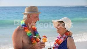 Elderly couple talking with cocktails