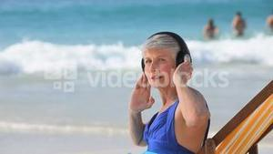 Aged woman listening to music on the beach