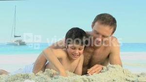 Father helping his son to build a sand castle
