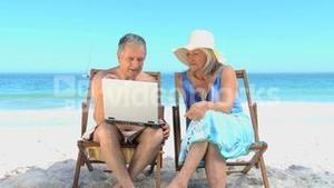 Elderly man showing to his wife a video on the laptop