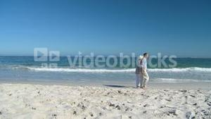 Elderly man walking on the beach wither his wife