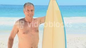 Elderly man looking at the beach with a surfboard