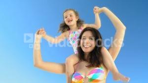 Attractive mother carrying her daughter on her shoulders