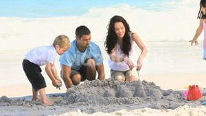 Parents building a sand castle with their children