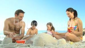Happy parents building a sand castle with their childs
