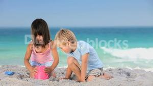 Cute boy building a sand castle with his sister