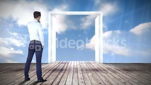 Door opening to blue sky watched by businessman