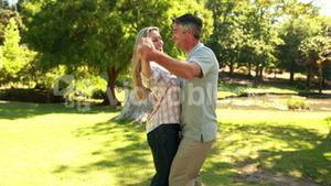 Happy couple dancing in the park