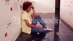 Depressed student sitting on the floor