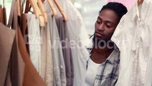 Male fashion designer looking at rack of clothes