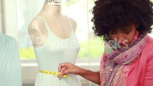 Fashion designer measuring dummy waist