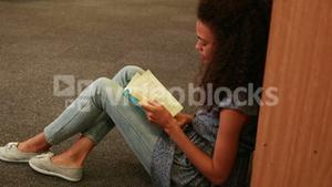 Focused student reading a book lying  on the floor