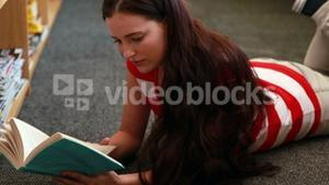 Beautiful student reading a book lying on the floor