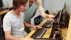 Teacher helping student with computer