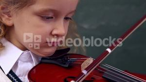 Cute pupil playing the violin
