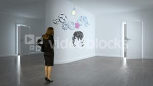 Businesswoman watching cog and wheel on wall