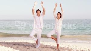 Peaceful couple meditating at the beach