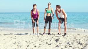 Friends running together on the beach