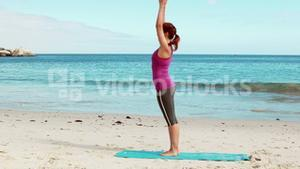 Woman doing yoga on the beach