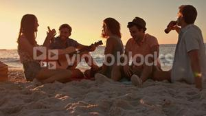 Friends sitting at the beach and playing guitar