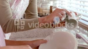 Mother and daughter washing up together