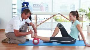 Physiotherapist using foam roller with patient