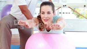 Physiotherapist using exercise ball with patient