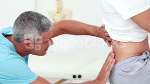 Physiotherapist checking a patients back