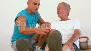 Trainer and old man doing a relaxation exercise