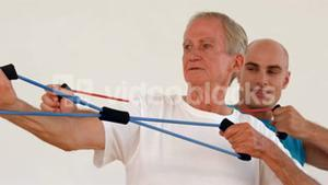 Trainer and old man exercising with resistance band