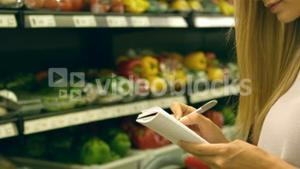 Woman checking her list while grocery shopping