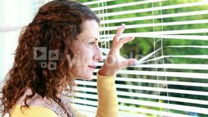 Woman peering through roller blind