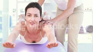 Trainer with woman on exercise ball