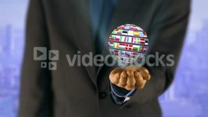 Ball made of European nationals flags turning on businessman hands
