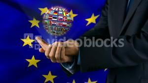 Ball made of European nationals flags turning on hands in front of European flag