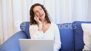 Happy woman using laptop on sofa and answering phone