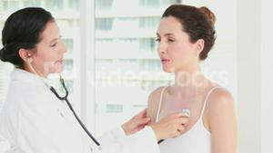 Doctor listening to patients chest with stethoscope