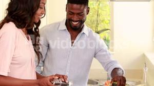 Pretty couple smiling and cooking