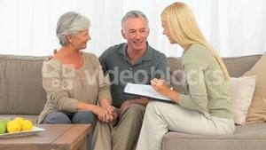Mature couple answering to a commercial woman