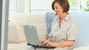 Elderly woman working on her laptop