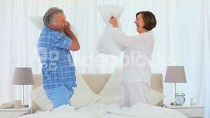 Retired couple playing on the bed with their pillows