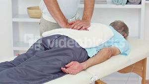 Doctor pressing on his patients back