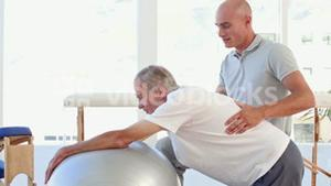 Doctor helping his patient to stretch with exercise ball
