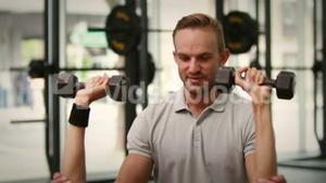 Fit woman lifting dumbbells with trainer