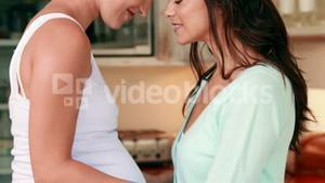 Lesbian expecting couple hugging